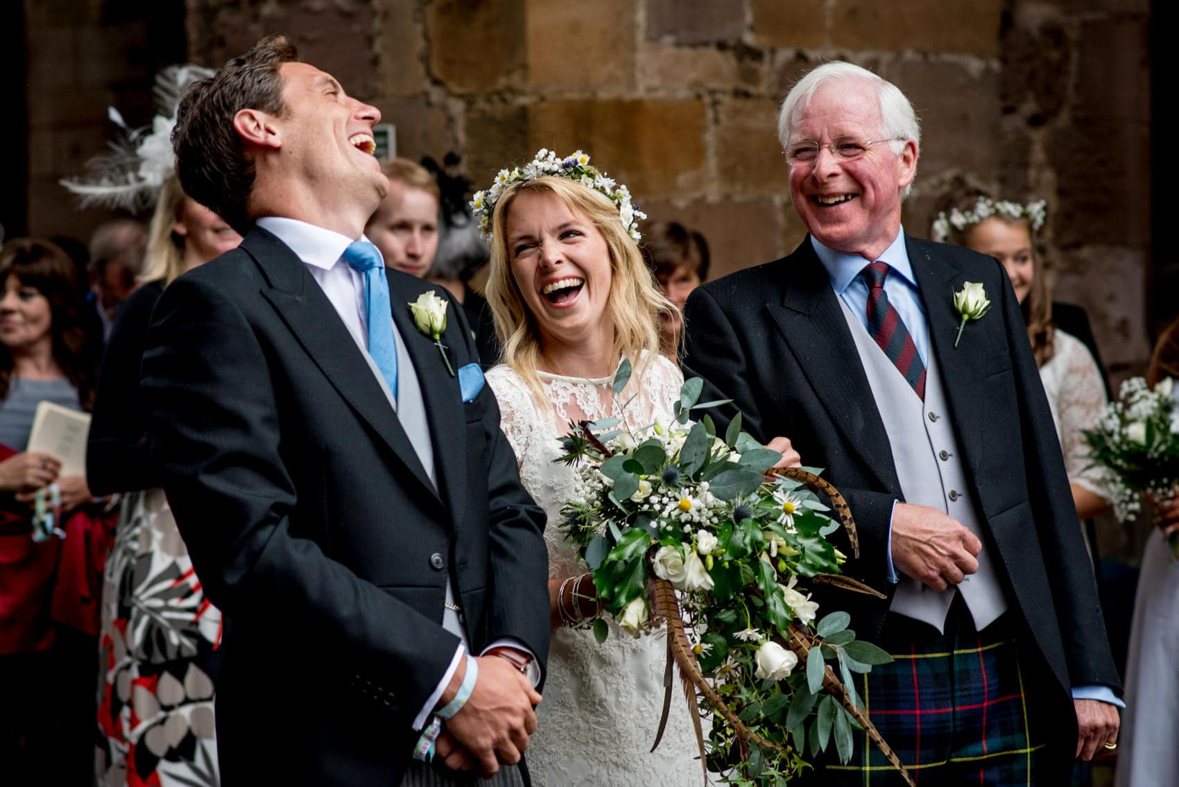 bride, her father and groom laughing at Melrose Abbey for her festival wedding